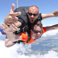 Tandem skydiving instructor rocking out in mid free fall