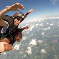 Tandem skydiving student and instructor with their arms in the air