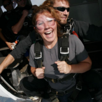 Happy tandem skydiving student about to jump from a plane