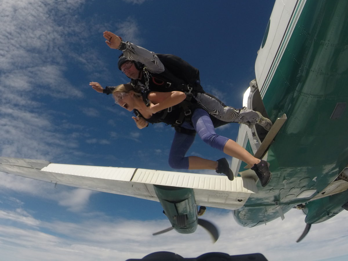 Tandem skydiving student screams for joy while instructor hurls them out of the plane