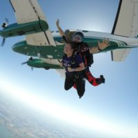 Tandem skydiving instructor spreading his arms as they jump from the plane