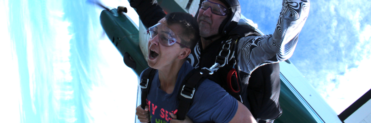 Tandem skydiving student holds on to his harness