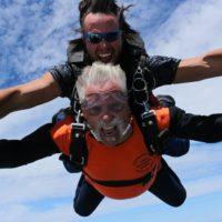 Older tandem skydiving student yelling for joy