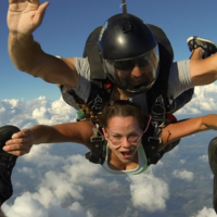Tandem skydiving student holding onto her instructors feet