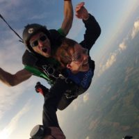 Tandem skydiving student hold onto instructors arm
