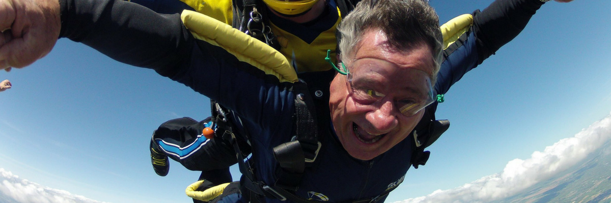Tandem skydiving student smiles as he flies through the air with his instructor