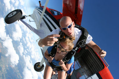 Tandem skydivers jumping out of a plane