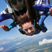 Tandem skydiving student smiles as the wind rushes past her