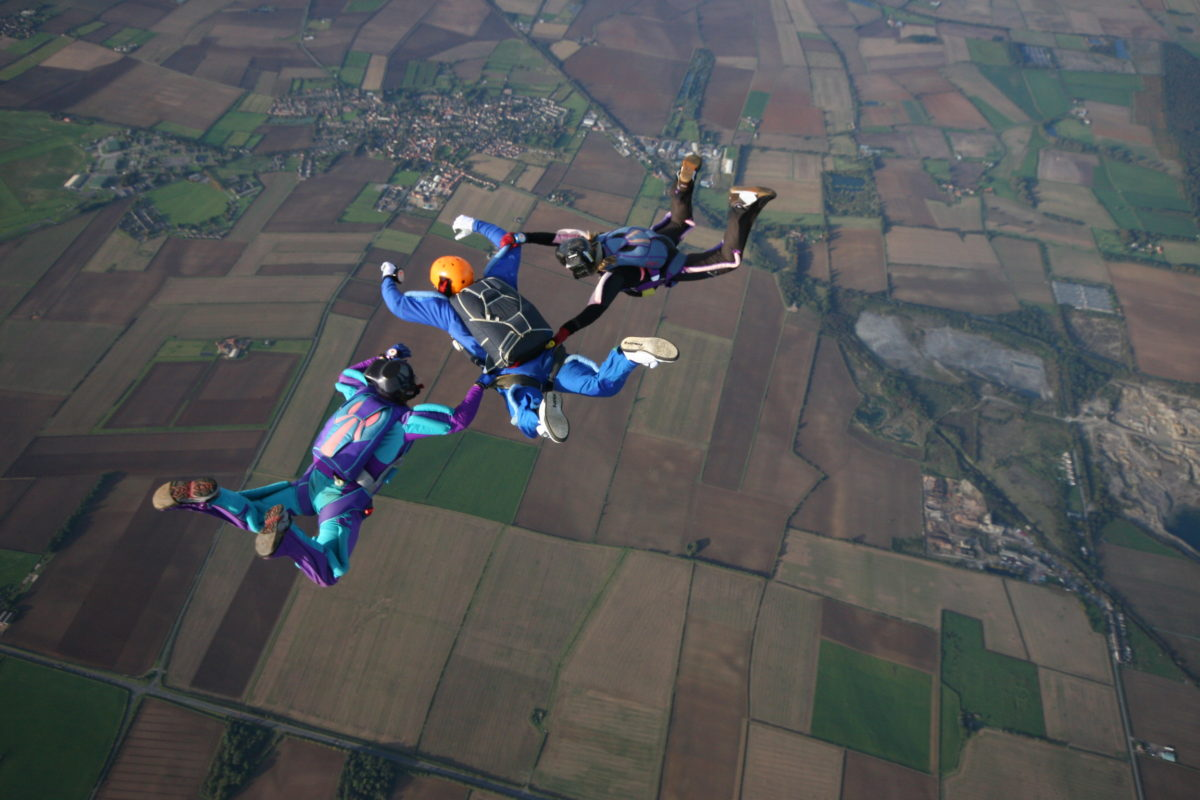 Skydivers making a 3-person formation