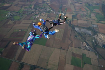 Three skydivers making a formation during free fall