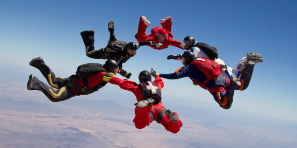Skydivers holding hands in a circle while free falling