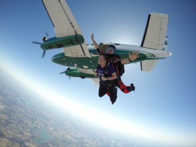 Skydiving instructor spreads his arms while jumping from a plane