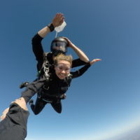 Tandem skydiver smiling at the camera while in free fall