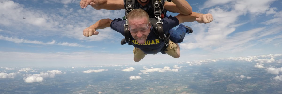 Tandem skydiving student sticks out his tongue during free fall