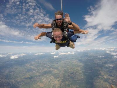 Tandem skydiving instructor waving at the camera during free fall