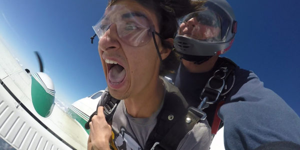 Tandem skydiving student holding on tight and yelling