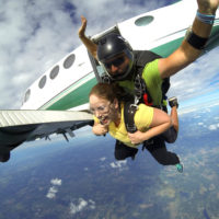 Tandem skydivers jumping out of an airplane on a gorgeous day
