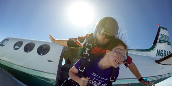 Tandem skydiving student hold on tight as the instructor jumps