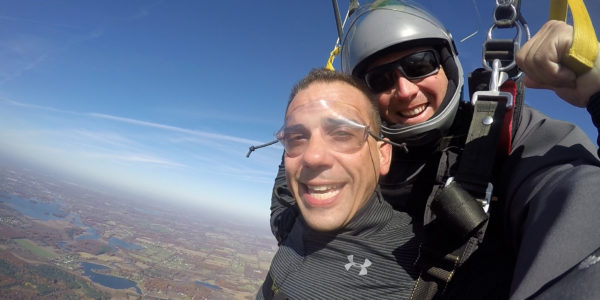 Tandem skydivers smiling at the camera during their parachute ride