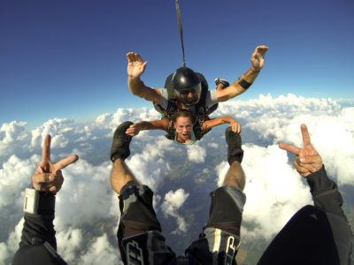 Tandem skydiving student grabs instructors feet during freefall