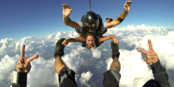 Tandem skydiving student holding onto instructors feet