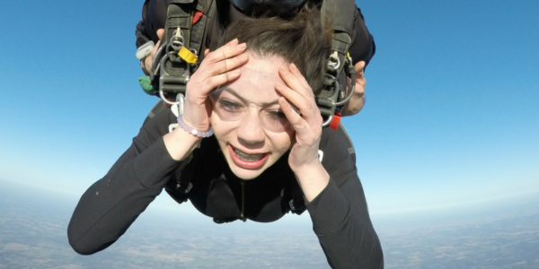 Tandem skydiving student holding her face