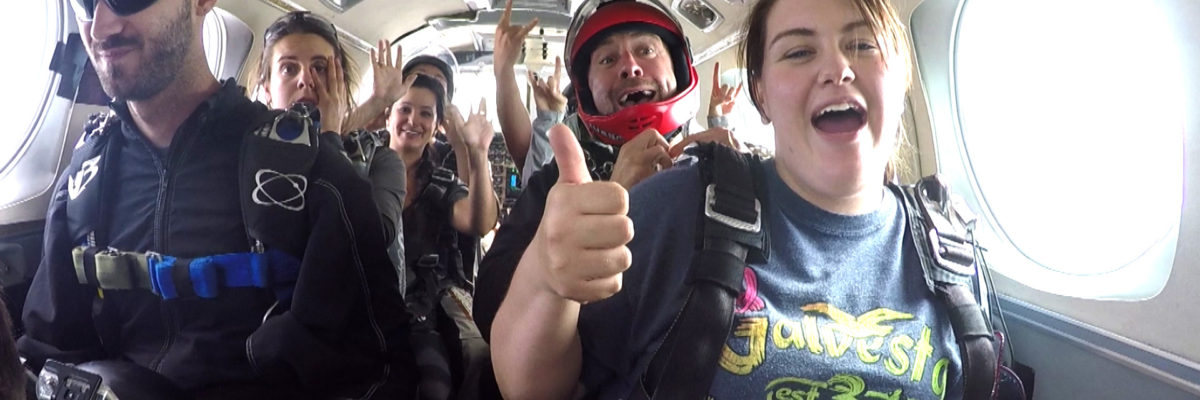Skydivers giving a thumbs up during the plane ride