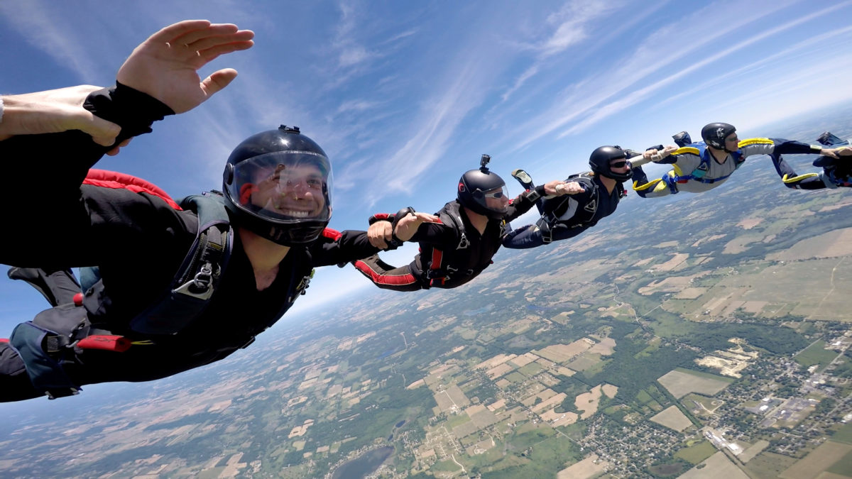 A group of skydivers locking arms to make a formation