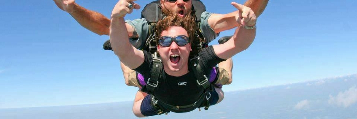 Tandem skydiving student yelling in mid free fall
