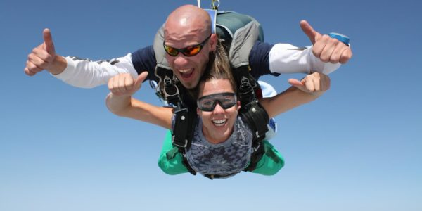 Tandem skydiving instructor and student giving their free fall two thumbs up