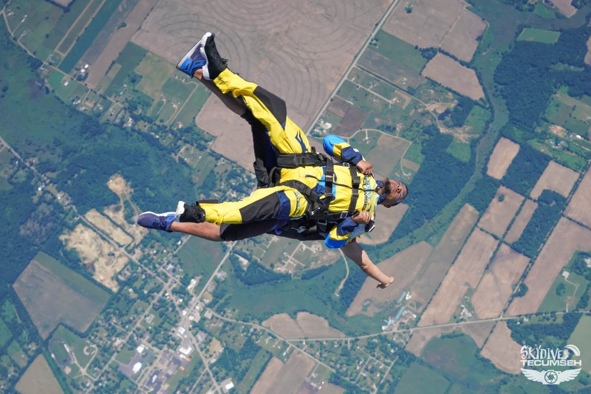 A tandem skydiving pair falling out of the aircraft into free fall